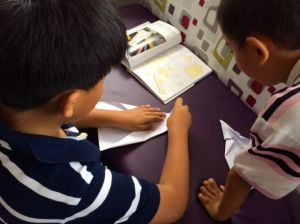 Two boys using their visual literacy skills to learn the finer details of paper plane making. Their dialogue is in Chinese, their descriptions to me in English and the motivation extremely high to refine their design skills.