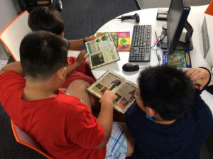 A group of boys sitting at the reference desk using Minecraft books written in English as a focus of discussions in Lao, Chinese & English about details of the game I am still trying to catch up on.